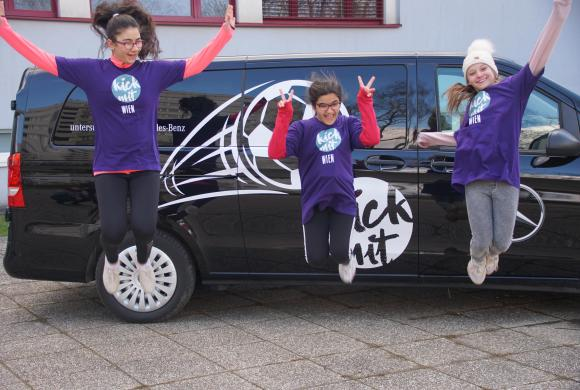 3 Mädchen springen vor dem Mercedes Auto