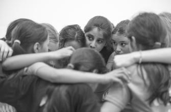 Mädchen stehen im Kreis und umarmen sich
