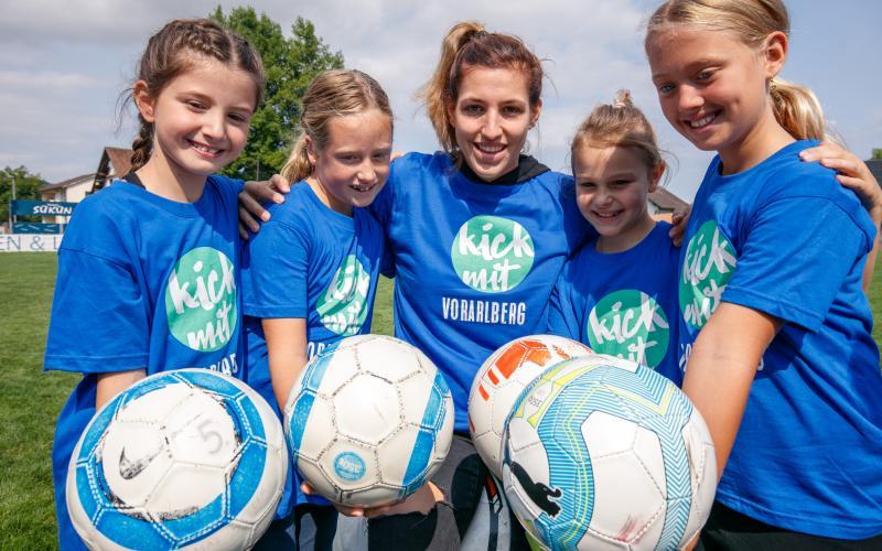 Lisa Makas mit vier Mädchen, alle halten einen Ball in die Kamera