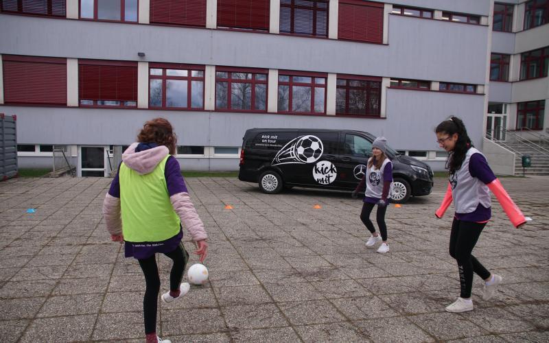3 Teilnehmerinnen spielen im Schulhof