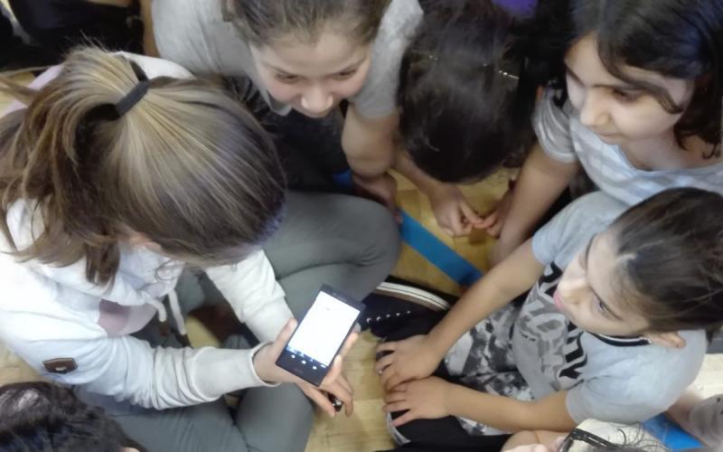 Mädchen hören gespannt die Radiosequenz über das Smartphone